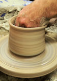 Potters hand in pot. Potter raising pot with hand in inside moulding clay Royalty Free Stock Photos