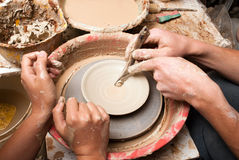 A potters hands guiding pupil hands to help him Stock Images