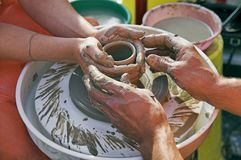 Potters' hands guiding woman's hands Stock Images