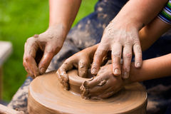 Potters team. A potters hands guiding a child hands to help him to work with the ceramic wheel Royalty Free Stock Images