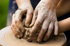 Potters team. A potters hands guiding a child hands to help him to work with the ceramic wheel Royalty Free Stock Photos