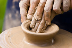 Potters team. A potters hands guiding a child hands to help him to work with the ceramic wheel Stock Image