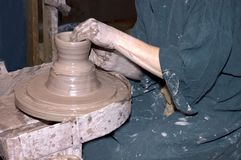 Potters Wheel, Artist Creating. The hands of the potter carefully mold a small pot as the wheel turns. When the item is ready, it will be fired in a kiln stock photography