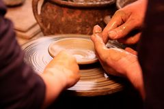 Potters working. With clay bowl on potter's wheel Royalty Free Stock Images