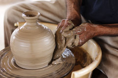 The pottery. Potters hands creating a clay masterpiece at the turning wheel Royalty Free Stock Photography