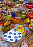 Pottery, Aix-en-Provence France. Bright, colorful ceramic bowls, plates, mugs, cups, and pitchers, are scattered on the ground in an outdoor marketplace in Aix Royalty Free Stock Image