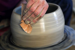 Pottery. Artist shaping a bowl on a pottery wheel. Shallow depth of field with focus on the fingers. Motion blur on the spinning bowl and wheel Stock Images