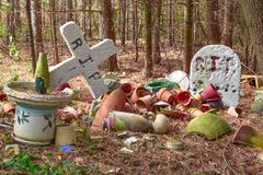 Pottery Cemetary. Broken pottery all laying on the ground with a RIP tombstone and cross Stock Photo