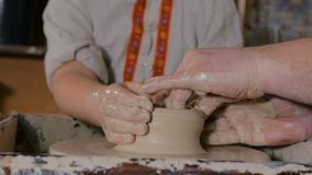 Potter showing how to work with ceramic in pottery studio stock video footage