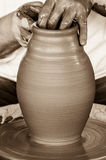 Hands working on pottery wheel. Clay pot in the making stock photo