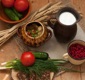 A pottery of cooked vegetables, a crock of milk, a wooden board with a tomato, cucumbers, bread and greens on a wooden surface Royalty Free Stock Photography