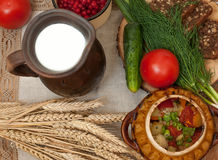 A pottery of cooked vegetables, a crock of milk, a wooden board with a tomato, cucumbers, bread and greens on a wooden surface Royalty Free Stock Photos