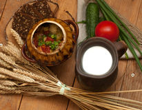 A pottery of cooked vegetables, a crock of milk, a wooden board with a tomato, cucumbers, bread and greens on a wooden surface Royalty Free Stock Image