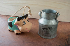 Pottery cow pot want to drink milk in milk bucket Stock Photography