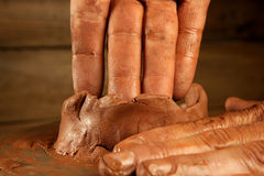 Pottery craftmanship clay pottery hands work. Pottery craftmanship red clay potter hands work finger closeup royalty free stock photography