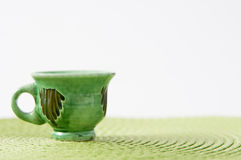 Pottery cup background. Old pottery cup on a green fabric background Royalty Free Stock Photo