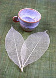 Pottery cup and leaves Stock Photography