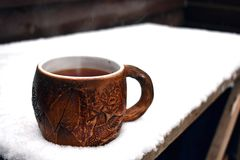 A pottery cup of steaming black tea in the falling snow royalty free stock photo