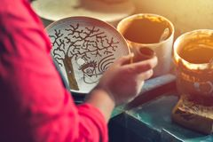 A pottery decorator painting a ceramic plate with vintage motifs in his work. Vintage look, sunset light.  Stock Photo