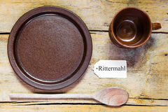 Pottery dishes and spoon on old wooden table, note with german w Royalty Free Stock Photography