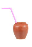pottery glass with pink drinking straw  on white Royalty Free Stock Image