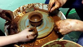 Pottery hands creating an earthen jar on a spin wheel stock footage