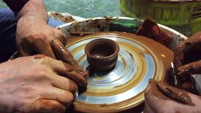 Pottery hands creating an earthen jar on a spin wheel stock video footage