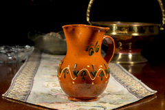 Pottery jug to serve wine or water on an embroidered table mat Stock Photo
