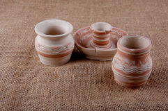 Pottery. Jugs and candlestick made of clay on sackcloth background royalty free stock photos
