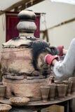 Pottery kiln. Old pottery kiln and clay mugs Royalty Free Stock Image