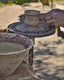 Pottery Maker. Hands with clay working on a rotating cup royalty free stock photo