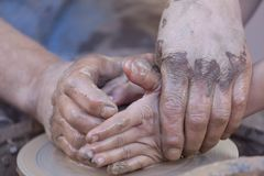 Hands working on pottery wheel. Pottery making, close up on hands. Hands working on pottery wheel Royalty Free Stock Image