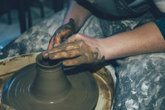 Pottery making, dirty hands in wet clay. Apron, pottery wheel, close up of craftsperson. Ceramic handmade in workshop royalty free stock photos