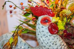 Pottery rooster head in front of flower arrangement - selective focus royalty free stock image