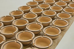 Pottery. Rows of ceramic ashtrays on old wooden table, gray background Royalty Free Stock Images