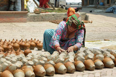 Pottery Square in Bhaktapur town, Nepal. BHAKTAPUR, NEPAL - APRIL 20, 2016: hindu woman working in pottery stand in the middle of Pottery Square in medieval town Royalty Free Stock Images