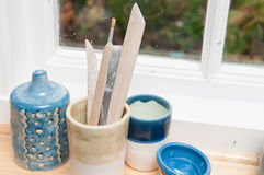 Pottery tools and vases on a window ledge stock photography