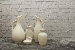 Pottery, vase, jug of white clay on a gray stone background. Pottery mock-up made from white clay on a gray background. stock photography