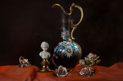 Pottery vase with some porcelain flowers. A simple composition, a pottery vase with some artistic objects: a porcelain bust and some porcelain flowers. The royalty free stock photo
