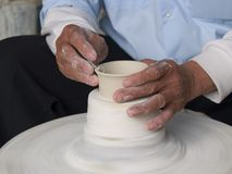 Pottery Wheel. Piece of clay turns as the hands of the pottery worker are shaping the clay Royalty Free Stock Photography