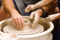 Pottery Wheel. Adult and child hands shaping a pot on a turning pottery wheel royalty free stock photos