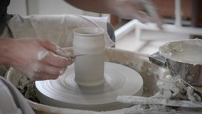 Pottery wheel turning, making vase of white clay ceramic clean hand person stock video