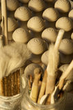 Pottery workshop details. Close up of unfired door knobs and brushes Stock Photo