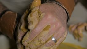 Pottery workshop. Hands of grandpa teaches granddaughter pottery