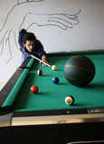 Potting a Basketball. An impossible game of pool.  One of the balls is a basketball, which, off course, is too big for pool Royalty Free Stock Images