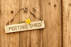 Potting Shed. Sign on wooden background with daffodil flower Stock Photo