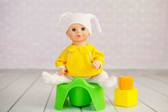 Potty training concept using a doll and toy potty Stock Photography