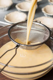 Pou the egg custard mixture into a strainer. Royalty Free Stock Photo