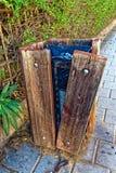 Poubelle avec une planche en bois coudée et une boîte de fer Image libre de droits