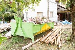 Poubelle de déchets de construction avec des charges au chantier de construction images libres de droits
